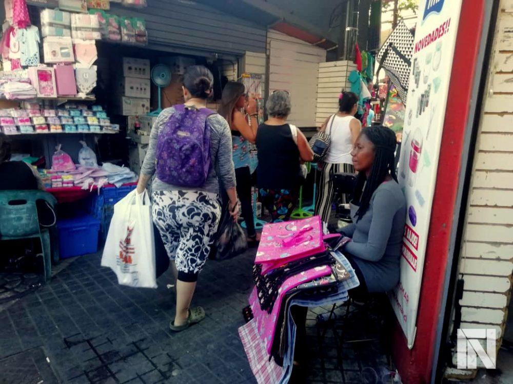 La haitiana Marie dejó Puerto Príncipe por el oasis chileno; ahora vende bolsas en un comercio santiaguino.