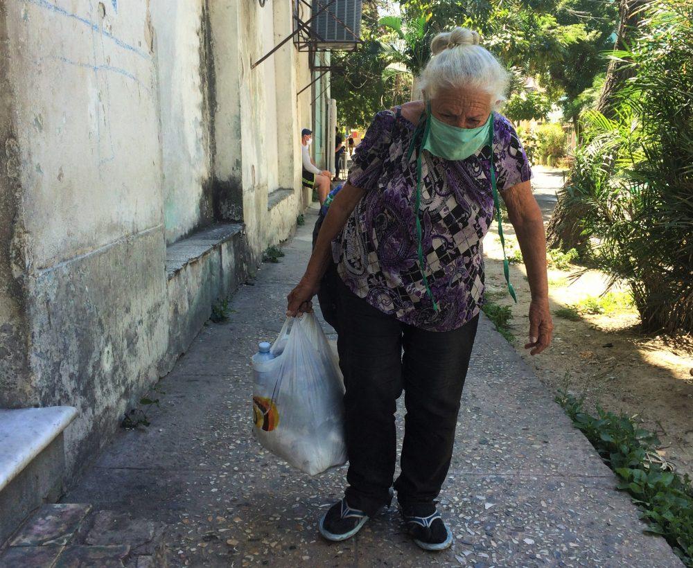 Una anciana carga sus compras en Santa Clara en medio de la pandemia de COVID-19
